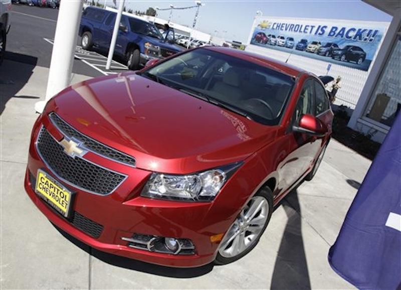 In this Aug. 30, 2011 photo, a 2011 Chevrolet Cruze is featured at a car dealership in San Jose, Calif. General Motors Co. said Thursday, Feb. 16, 2012, it made more money in 2011 than any year in its history. (AP Photo/Paul Sakuma)