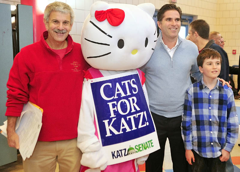 State Senator Roger Katz, left, a costumed campaigner, Tagg Romney and his son Joe pose for a photo before the Kennebec County Super Caucus at Farrington School in Augusta on Saturday.