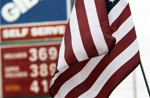 An American flag flaps in front of gas prices posted at a gas station in Topsham today. A price-monitoring website is warning Maine motorists that gasoline prices could rise sharply during the next few days.