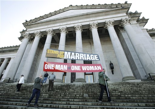 "In ths Jan. 23, 2012, photo, Ken Jackson, right, and Don Taylor carry a sign that reads ""Stand Up For Marriage – One Man + One Woman"" following a rally at the Capitol in Olympia, Wash."