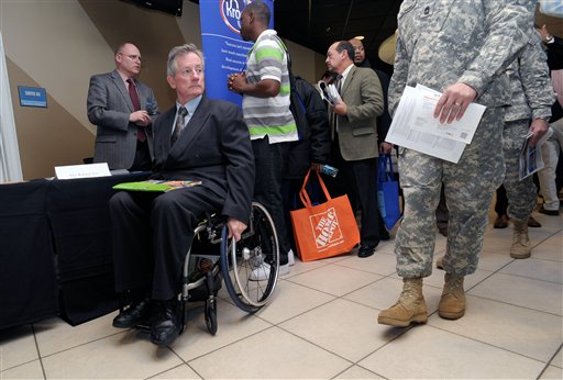 In this Feb. 9, 2012, file photo, disabled army veteran Ken Higgins, of Lilburn, Ga., finishes with a recruiter as he and other veterans attend a military-to-civilian job and education fair held at Turner Field, in Atlanta. General Electric Co. plans to hire 5,000 veterans over the next five years and invest $580 million to expand its aviation business.