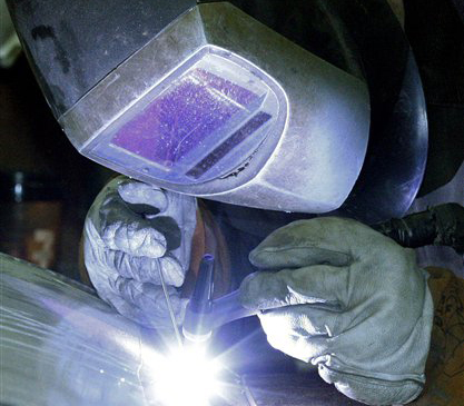 A workman welds a stainless steel tank at JV Northwest, in Camby, Ore., on Monday. Busier factories are helping drive the economy.