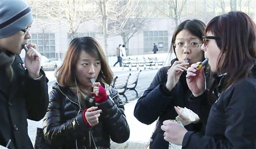 In this Monday, Jan. 23 photo, students try free samples of AeroShot, an inhalable caffeine packed in a lipstick-sized canister, on the campus of Northeastern University in Boston. Harvard University engineering professor David Edwards, created AeroShot, which went on the market in late January. (AP Photo/Rodrique Ngowi)