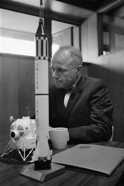 In this Feb. 8, 1963 file photo, astronaut John Glenn sits with models of the Mercury spaceship atop its launch rocket and a lunar module. (AP Photo/Ed Kolenovsky) Bow Tie;Close Up;Cup;NASA;National Aeronautics and Space Administration;Politician;Politics;Profile;Seated;Senator;Sitting