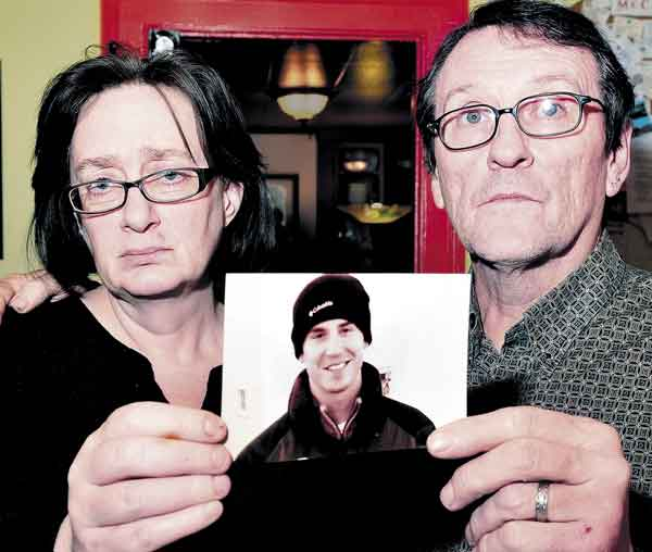 TRAGIC END: Lorna and Michael Smilek hold a 2006 photograph of Michael's son, Justin Crowley-Smilek, who was shot and killed in November after he confronted Farmington police.