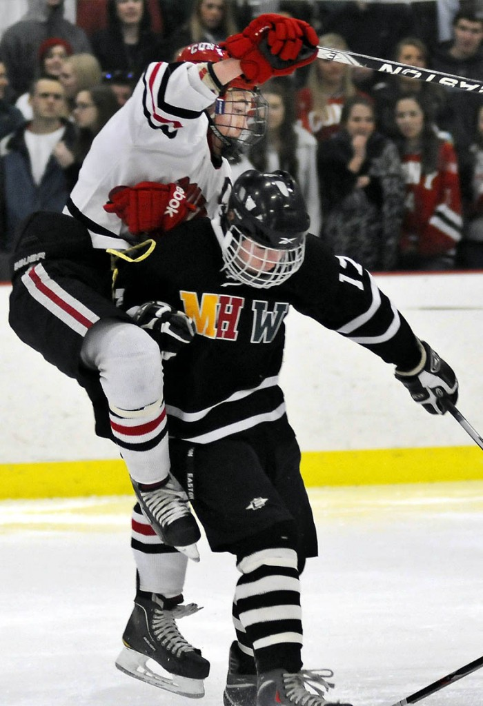 FACE OFF: Cony High School's Blane Galen Casey, left, bounces off of MHW's Zach Glazier during a hockey match up Tuesday in Readfield.