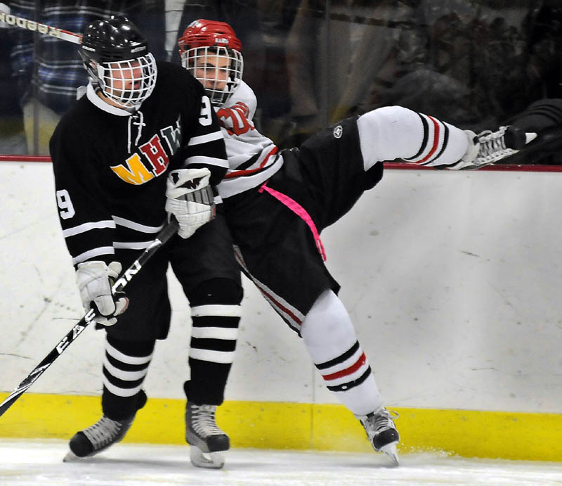 FACE OFF: Cony High School's Austin Davis, right, rides the boards while being checked by MHW's Jarred Hanson during a hockey match up Tuesday in Readfield.