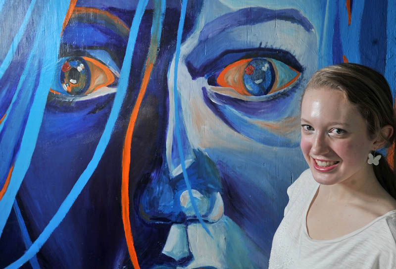 """YOUNG ARTIST: Margaret Robe, a senior at Waterville Senior High School, poses for a portrait next to her painting titled, """"Put Out the Fire"""" at school on Friday. Robe's painting was selected as one of 20 pieces of artwork to be featured on the Maine Learning Technology Initiative laptop screensaver in 2012-13."""