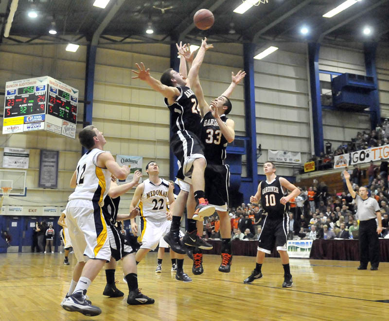 Photo by Michael G. Seamans Gardiner High School's Matt Hall, 24, and Aaron Toman, 33, jump for the rebound in the first half of the Eastern Class B semi-finals at the Bangor Auditorium Wednesday. Gardiner defeated Medomak Valley 57-46.