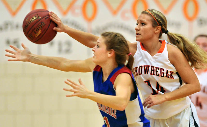 BATTED AWAY: Skowhegan Area High School's Amanda Johnson, right, gets a hand on the ball as she defends Messalonskee High School's Nicole Collier in the first quarter Friday night in Skowhegan.