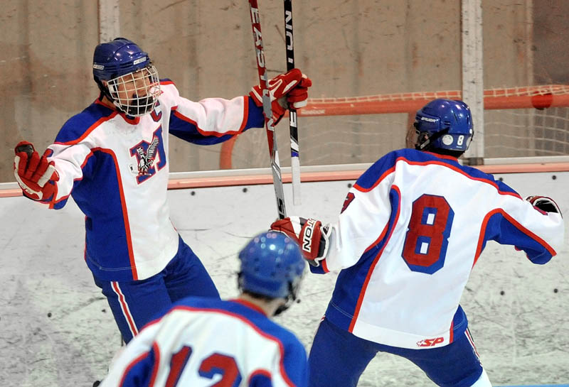 Messalonskee High School's Sam Dexter, 7, facing, turns to celebrate a goal with teammates Billy Blake, 8, right, and Chase Cunningham, 12, in the first period against John Bapst Memorial High School in an Eastern B regional quarterfinal game at Sukee Arena in Winslow Tuesday night.