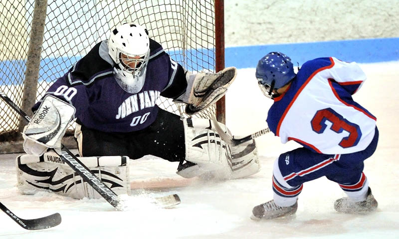 Messalonskee High School's Joshua Towle, 3, scores on John Bapst Memorial High School goalie Jaron Leonard, 00, in the first period in an Eastern B regional quarterfinal game at Sukee Arena in Winslow Tuesday night.