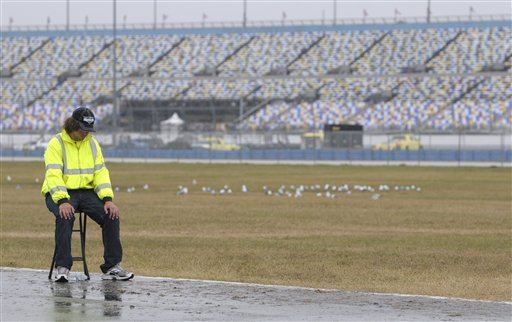 Parking attendant Tyler Bounelis, of Ormond Beach, Fla., sits near an empty parking lot at Daytona International Speedway in Daytona Beach, Fla., today.
