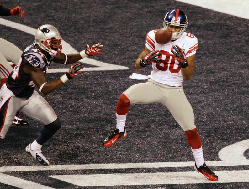 New York Giants wide receiver Victor Cruz makes a catch for a touchdown as New England Patriots safety James Ihedigbo defends during the first quarter of Super Bowl XLVI in Indianapolis.