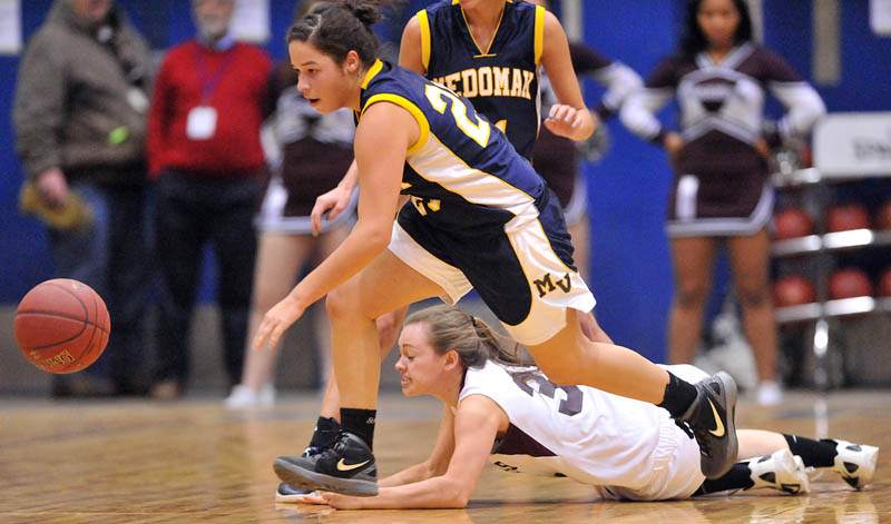 Photo by Michael G. Seamans Medomak Valley High School's Amanda Hendrickson-Belloguet, 25, chases down the ball as Nokomis High School's Taylor Shaw, 32, dives in the first half of the Eastern Class B quarterfinals game at the Bangor Auditorium Saturday. Nokomis defeated Medomak Valley 58-51.