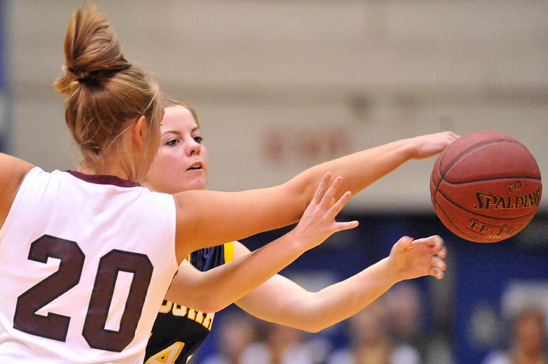 Photo by Michael G. Seamans Nokomis High School's Emilee Reynolds, 20, gets a hand on the ball as Medomak Valley High School's Taylor Simmons, 14, tries to pass in the second half of the Eastern Class B quarterfinals game at the Bangor Auditorium Saturday. Nokomis defeated Medomak Valley 58-51.