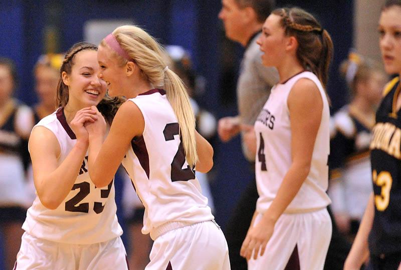 Photo by Michael G. Seamans Nokomis High School teammates Kelsie Richards, 23, left, and Lindsay Whitney, 22, center, celebrate after defeating Medomak Valley 58-51 in the Eastern Class B quarterfinals game at the Bangor Auditorium Saturday.