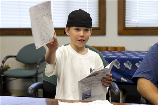 Nine-year-old West James shows off the diary he kept while sailing across the Pacific on Thursday in Honolulu. James, his father, and uncle were attempting their first voyage across the Pacific in a sailboat when rough seas damaged their boat hundreds of miles from land.