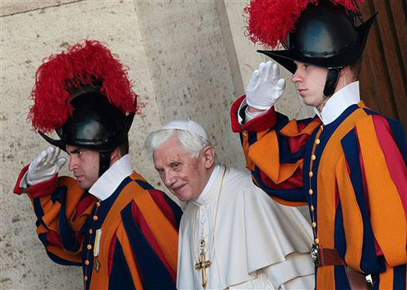 Pope Benedict XVI is saluted by Swiss guards as he leaves the Synod hall after a meeting with Cardinals and Bishops at the Vatican on Friday, Feb. 17. The Pontiff is scheduled to name 22 new Cardinals in a Consistory, Saturday Feb. 18, at the Vatican. (AP Photo/Gregorio Borgia)