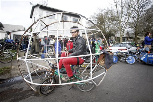 """Zane Fischer sits in his hamster ball bike before the start of the Chariot Wars on Saturday in Portland, Ore. He competed for the pleasure of hoisting a 3-foot-tall, homemade, skull-bearing piece of welded junk called the """"Ben Hurt"""" trophy."""