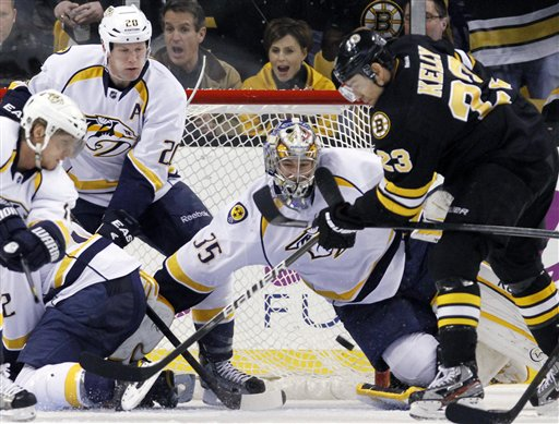 Boston Bruins' Chris Kelly (23) tries to get a shot off in front of Nashville Predators' goalie Pekka Rinne (35) as the Predators' Ryan Suter (20) defends in the third period Saturday in Boston. The Bruins won 4-3 in a shootout.
