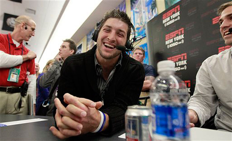 Denver Broncos quarterback Tim Tebow, left, laughs during an interview on radio row at the Super Bowl XLVI media center on Thursday in Indianapolis. (AP Photo/David J. Phillip)