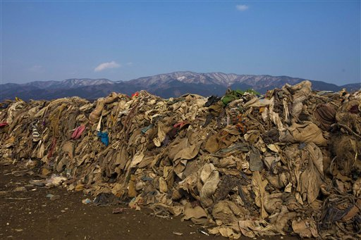 This Feb. 21, 2012, photo shows clothing lying in heaps at the site of a neighborhood destroyed by the 2011 earthquake and tsunami, in Rikuzentakata, Japan. Scientists believe 1 million to 2 million tons of lumber and other construction material, fishing boats and other fragments of coastal towns are still in the water and are being carried across the Pacific by ocean currents.
