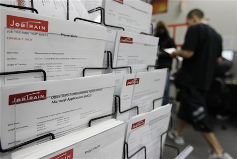 This Feb. 14 photo shows job postings at JobTrain employment center in Menlo Park, Calif. The number of people seeking unemployment benefits fell to the lowest point in almost four years last week, the latest signal that the job market is steadily improving. (AP Photo/Paul Sakuma)