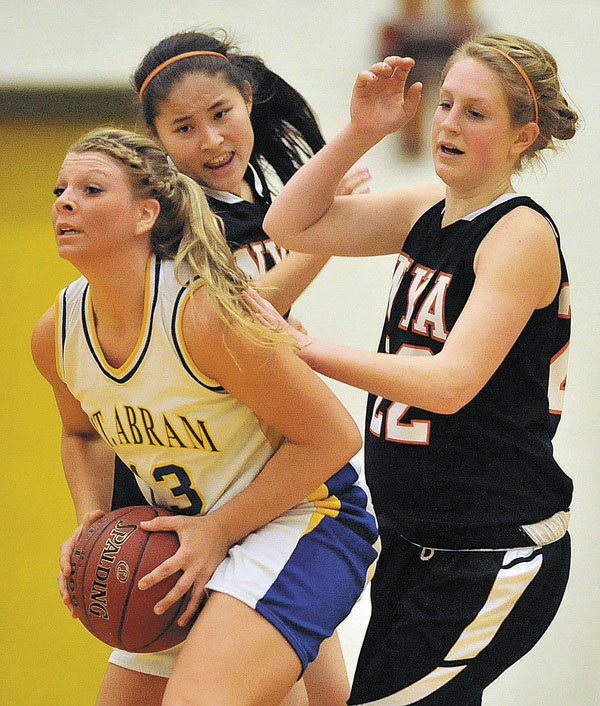 LOOKING FOR OPTIONS: Mt. Abram High School's Mikayla Luce, left, looks to pass while defended by North Yarmouth Academy's Lillie Reder, center, and Morgan Scully on Tuesday night in Salem Township. Mt. Abram won 52-35.