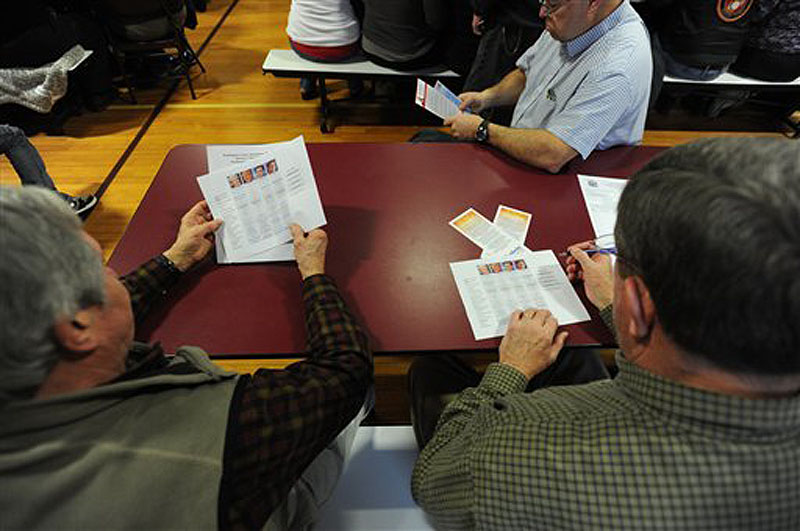 Republican voters Elton Anderson, left, of Milbridge and Gary Willey, right, review presidential comparison materials before the Washington County Republican Super Caucus on Saturday at Washington Academy in East Machias. More than 300 people cast ballots at the event.