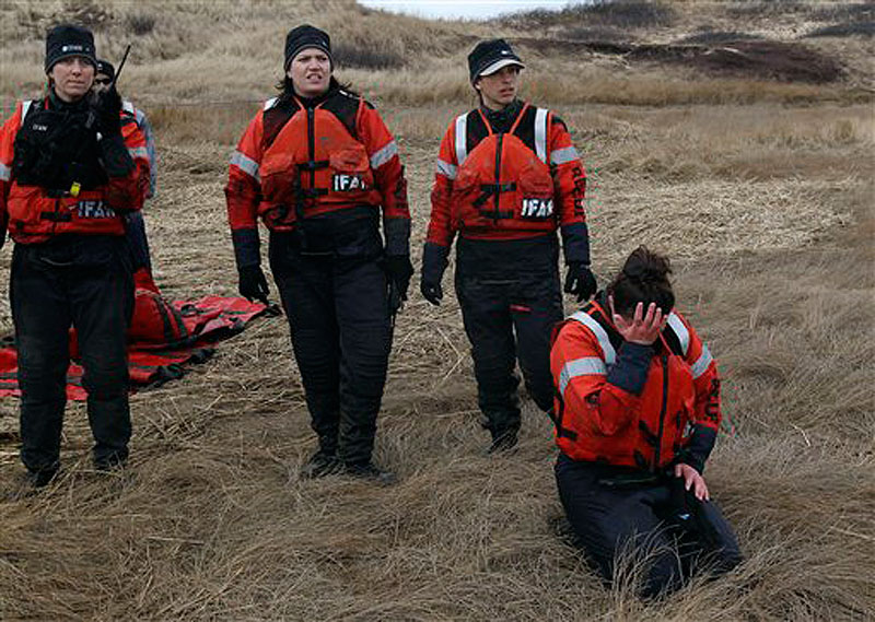 Linda D'eri places her head in her hand as Katie Moore, Misty Niemeyer and Kat Rose (left to right) watch a group of dolphins they rescued move away from the mud flat they were stranded on during low tide in Wellfleet, Mass., on Tuesday, Feb. 14, 2012. Ten of the dolphins were saved and one perished during the event. (AP Photo/Stephan Savoia)