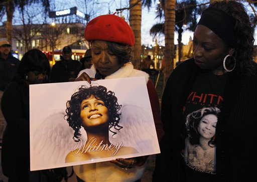 Whitney Houston fans, Lawanda Howkins, left, and Melanie Braggs honor her memory at a candlelight vigil in Leimert Park in Los Angeles on Monday.