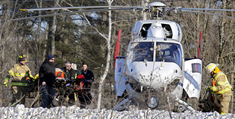 A patient from a motor vehicle accident that occurred Sunday on Route 202 in Winthrop is escorted to a helicopter for transport to a hospital.