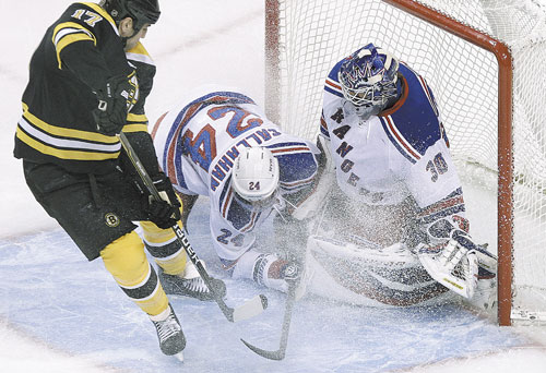 NICE STOP: New York Rangers right wing Ryan Callahan (24) dives in the crease as goalie Henrik Lundqvist protects the net against Boston Bruins left wing Milan Lucic, left, in the first period Tuesday in Boston.