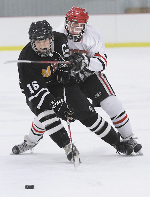 ONE MORE CLASH: MHW forward Tyler Bryant (16) battles for the puck with Cony High School's Austin Davis during the first period earlier this season in Kents Hill. The two teams will meet again in the Eastern Class A quarterfinals at 4 p.m. today at Kents Hill.