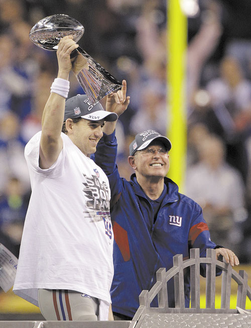 WE DID IT: New York Giants quarterback Eli Manning holds the Vince Lombardi Trophy with head coach Tom Coughlin after beating the New England Patriots in Super Bowl XLVI on Sunday in Indianapolis.