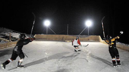 IT'S GOOD: Girls celebrate scoring a goal during a game of shinny hockey at John Hinkley's lighted rink in West Gardiner.