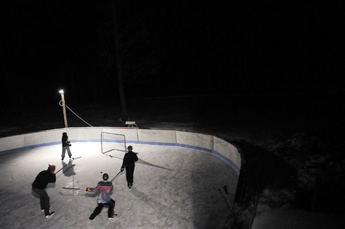 PLAYING FOR FUN: Kids play pickup hockey at Vaughn Smith's lighted rink at his home in West Gardiner.