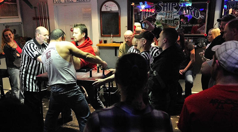 David Goulet, of Bangor, left, and Kurt Howgate, of Shapleigh, get ready to compete in the Maine State Arm Wrestling Championships on Saturday night at the Pond Town Tavern in Winthrop.