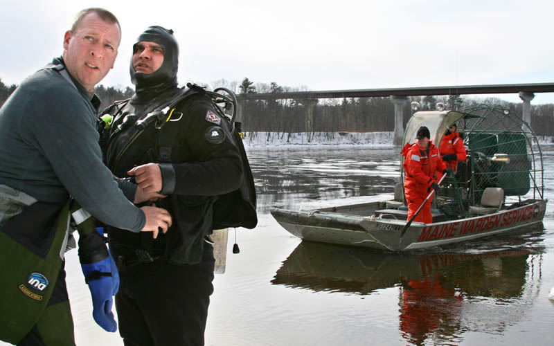 Dive Warden Robert Johansen, left, helps fellow diver Mike Pierre prepare today for a search of the Kennebec River below the Carter Memorial Bridge. Dive teams from the warden service and state police are searching two areas in Waterville for missing toddler Ayla Reynolds.