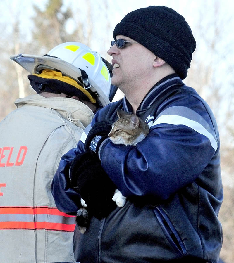 SAFE: Deril Stubenrod holds his rescued cat Mittens that firefighters pulled out of the burning home owned by his father Charles Stubenrod on Gogan Road in Benton on Thursday.