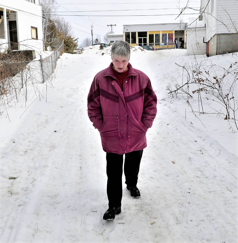 CLUES: Janice Gitschier walks the trail on Wednesday from Main Street in Bingham to Baker Street where she and Ernest Sayers were living. The trail had blood spots on it a short distance from where Sayers' body was found Sunday.