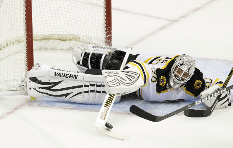 GET OUT OF HERE: Boston Bruins goalie Tim Thomas (30) swats away a shot during the first period against the Washington Capitals on Sunday in Washington. Thomas made 35 saves and the Bruins won 4-1.