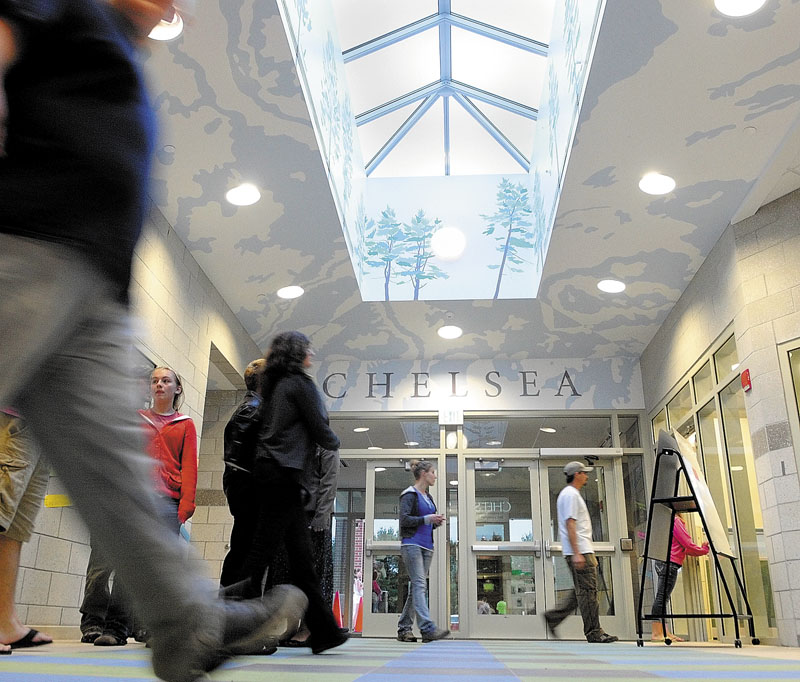 People walk through the lobby during an open house on Thursday night at the new Chelsea Elementary School. The lobby walls and ceiling are painted with trees and patterns inspired by topographical maps.