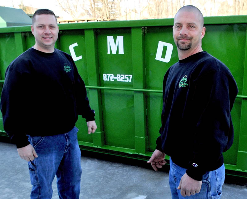 Mickey Wing, left, and his brother, Charlie Wing, stand beside one of the many Dumpsters used by Central Maine Disposal in Fairfield. The business has received the 2011 Business of the Year award from the Mid- Maine Chamber of Commerce.
