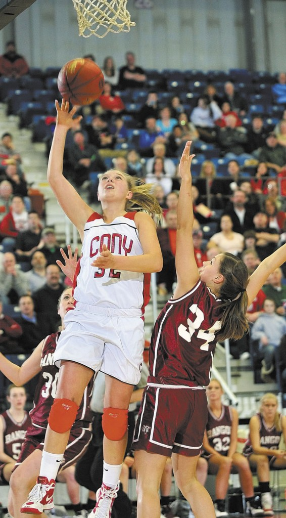Staff photo by Joe Phelan Cony's Mia Diplock goes up for shot over Bangor's Jordan Seekins during the Class A East tournament on Friday night at the Augusta Civic Center.