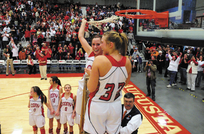 Cony Rams Julie Arbour and Mia Diplock celebrate by cutting down the net after winning the Class A East championship game on Friday night at the Augusta Civic Center.