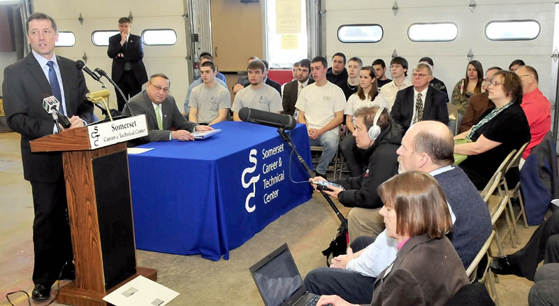 SCHOOL PROPOSAL: Education Commissioner Stephen Bowen, standing, and Gov. Paul LePage, seated at right, address students and educators at Somerset Career & Technical Center in Skowhegan on Wednesday.