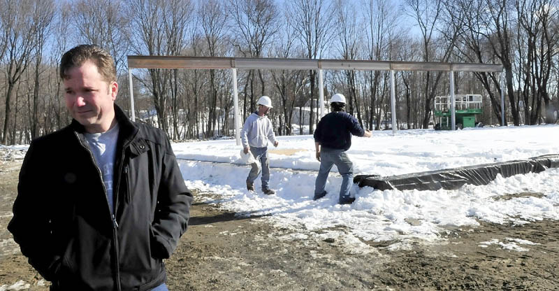 GOING UP: Project coordinator Tom Harling discusses the building of a new Family Dollar store as workers clear snow off the foundation at the site along Old Point Avenue in Madison on Monday.