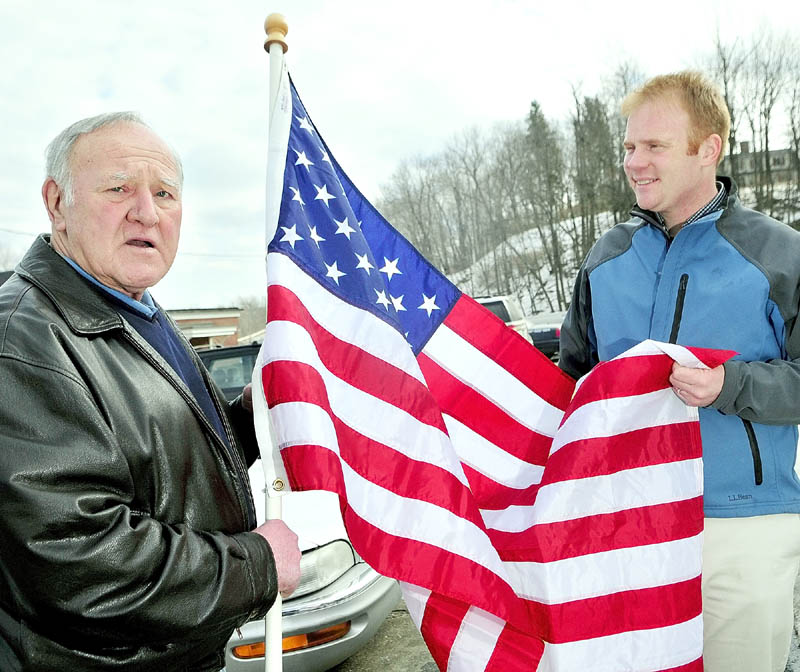 Jim Keenan, left, and Patrick Wright, executive director of Gardiner Main Street, hold up an American flag Keenan bought to show as example for his project of lining U.S. Route 201 in the city with them.